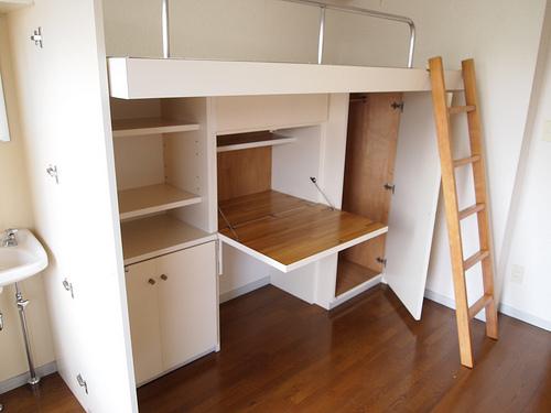 ベッドの下に机がある。隣には洗面台までついています。