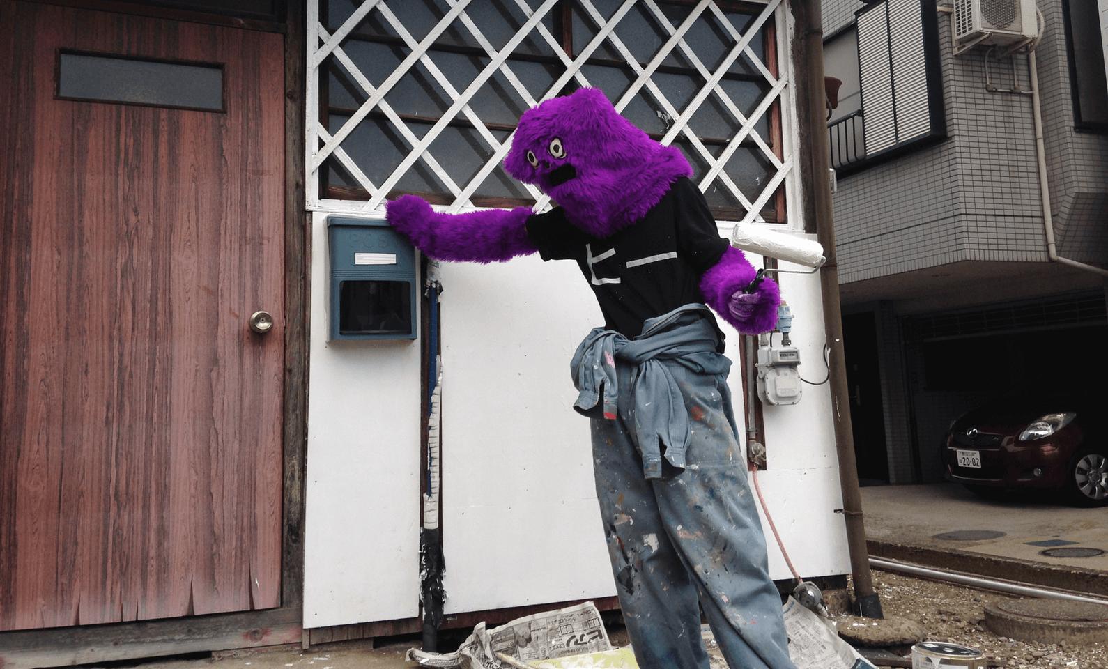 オレ・ゴーレムの子孫であるヒーレムの格好をしながら外壁を白く塗る松岡さん。