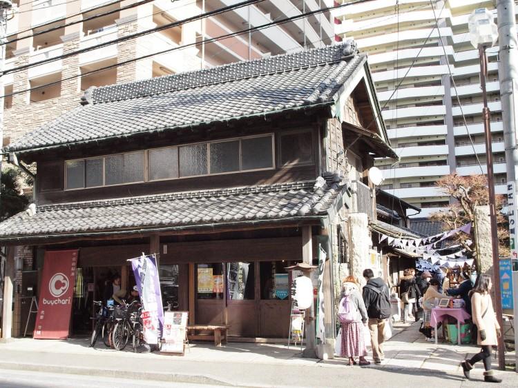 古民家スタジオ旧・原田米店。古民家と高層マンションとのコントラストが印象的です。