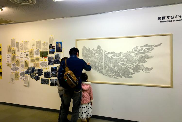 絵の中に描かれた松戸の街並や建物を読み解いている姿が印象的です。