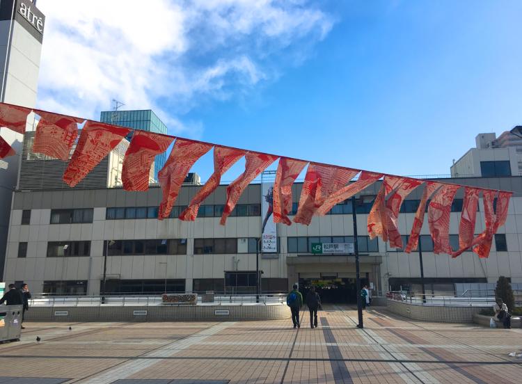松戸駅西口デッキにのぼりが出現!風に吹かれていて、何が描かれているのか一見するとわからないですが、立ち止まってよく見ると、松戸の街並や建築物が描かれていることがわかります。